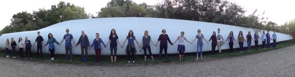 Sustainability students in front of a retired turbine blade.